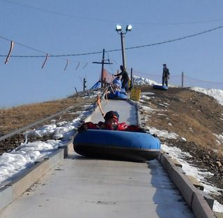 Peezer riding up the tube lift. Note the complete lack of snow on the ramp.
